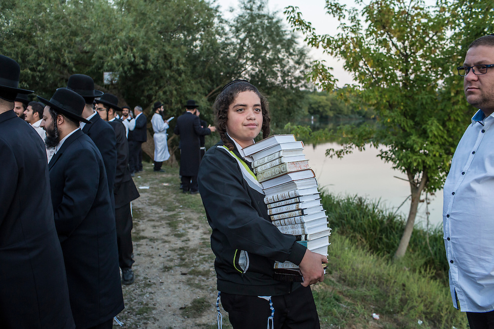 UMAN, UKRAINE - SEPTEMBER 14: A boy holds a stack of books as other Hasidic pilgrims pray near the burial site of Rebbe Nachman of Breslov on September 14, 2015 in Uman, Ukraine. Every year, tens of thousands of Hasidim gather for Rosh Hashanah in the city to pray at the holy site. (Photo by Brendan Hoffman/Getty Images) *** Local Caption ***
