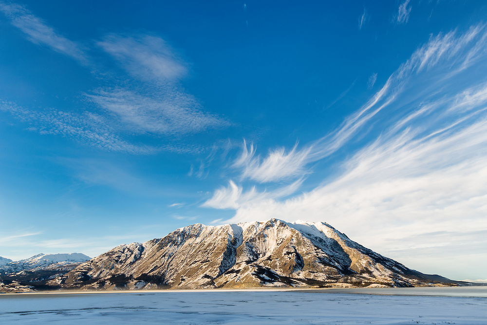 Cirrus clouds over Sheep Mountain along Kluane Lake in Kluane National Park in Yukon, Canada. Winter. Afternon.