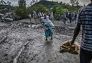 Woman navigates muddy road outside of food aid relief center set up by USAID to provide to Ethiopian Highlander families who, after the worst drought in decades now face torrential rains that threaten their crops this year.  Lalibela, Ethiopia