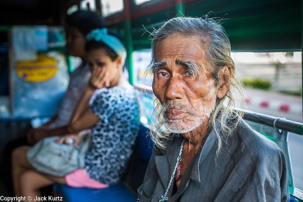 30 APRIL 2013 - MAHACHAI, SAMUT SAKHON, THAILAND:  An elderly Thai man on a truck converted to use as a bus in Mahachai, Samut Sakhon province, Thailand. Pickup trucks are frequently converted to use as buses by the installation of bench seats in the back. Called songthaews, they are common sight in Thailand. Conversion of large trucks is less common but happens in large towns with a large population of factory workers. Samut Sakhon has a very large population of Burmese migrant workers who work in the fishing industry and electronics factories in town.         PHOTO BY JACK KURTZ