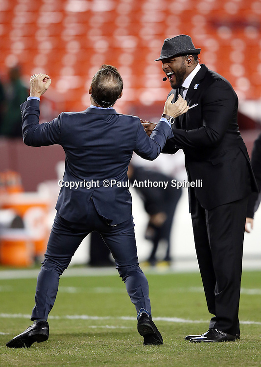 (L-R) Former San Francisco 49ers quarterback and current day ESPN television analyst Steve Young jokes around with former Baltimore Ravens linebacker Ray Lewis before the Washington Redskins 2015 week 13 regular season NFL football game against the Dallas Cowboys on Monday, Dec. 7, 2015 in Landover, Md. The Cowboys won the game 19-16. (©Paul Anthony Spinelli)