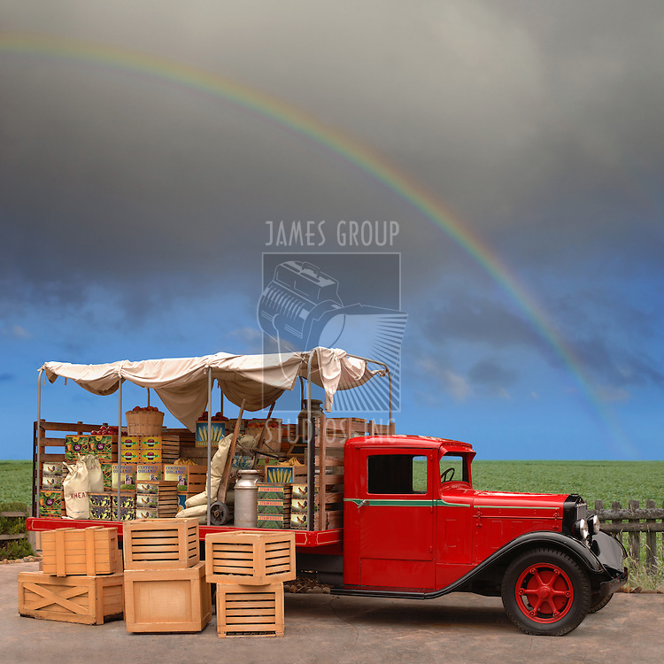 Vintage produce truck parked on the side of the road near a field with a rainbow in the background