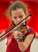 A student plays the violin during the dedication and ribbon cutting for the Mandarin Immersion Magnet School, October 24, 2016.