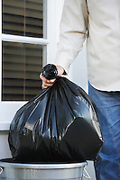 Man putting garbage bag into trash can mid section
