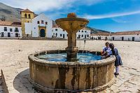 Villa De Leyva, Colombia  - February 8, 2017 : children playing at the fountain of Plaza Mayor of  Villa de Leyva Boyaca in Colombia South America