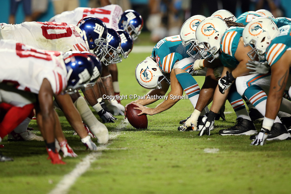 The Miami Dolphins offensive line gets set to snap the ball opposite the New York Giants defensive line during the NFL week 14 regular season football game against the New York Giants on Monday, Dec. 14, 2015 in Miami Gardens, Fla. The Giants won the game 31-24. (©Paul Anthony Spinelli)