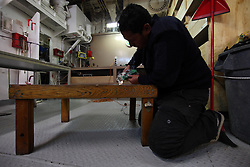 ATLANTIC OCEAN ABOARD ARCTIC SUNRISE 31MAY11 - Deckhand Tereapii Williams of New Zealnd works on a table engraving aboard the Greenpeace Ship Arctic Sunrise.....jre/Photo by Jiri Rezac / Greenpeace