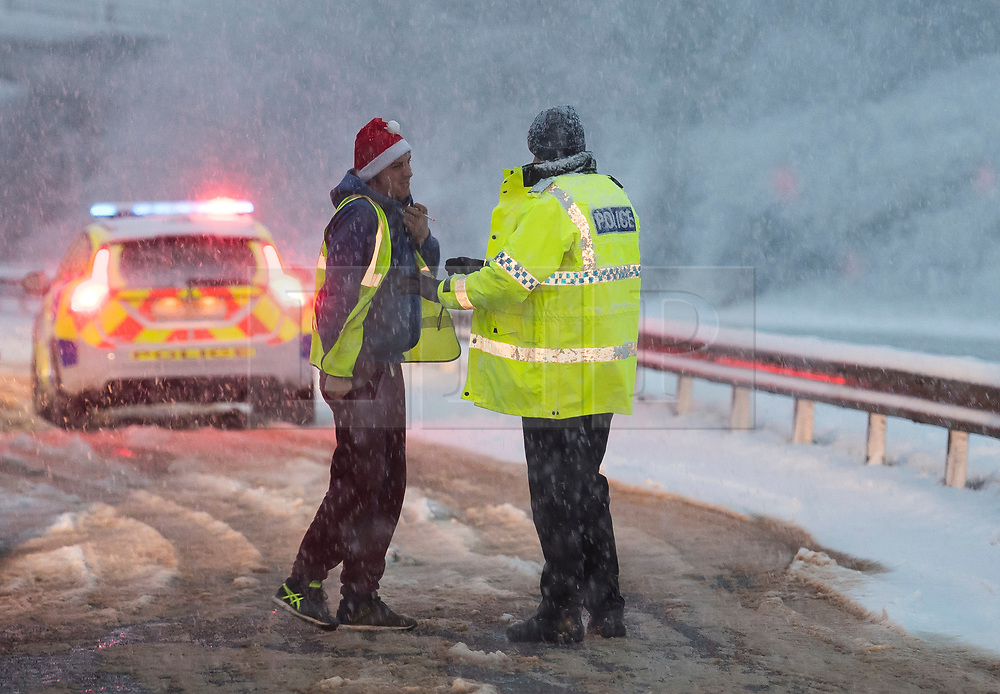 © Licensed to London News Pictures. 10/12/2017. Bourne End, UK. Police officers attend the scene of an incident on the A41 near Bourne End in Buckinghamshire where vehicles had spun on the road in heavy snow. The A41 north bound is currently closed. Oarts of the south east of England are blanketed with snow for the first time this winter. Photo credit: Ben Cawthra/LNP
