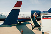 HUNTSVILLE, AL – APRIL 2, 2014: Ramp agent Tim Miller prepares a plane for departure at Huntsville International Airport. In an attempt to reverse the trend of declining service by airlines in small airports, Huntsville International Airport attempted to implement a rebate plan that would offer incentives to some carriers for enhanced service to the midsize city. The Federal Aviation Administration cautioned that the plan could potentially violate a federal law barring interference with airline fares, routes or service levels. When the industry's largest trade group, Airlines for America, threatened to, the airport's plan was disrupted. As major airlines continue to trim service offerings in smaller, less profitable cities, airports like Huntsville International struggle to attract and maintain carriers. CREDIT: Bob Miller for The Wall Street Journal<br />