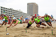 Aug 8, 2014; Virginia Beach, VA, USA; Competitors dive for the beach flags during the 2014 USLA National Lifeguard National Championships. Mandatory Credit: Peter J. Casey