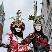 VENICE, ITALY - FEBRUARY 20:  Two women wearing Carnival costumes and masks pose in St Mark Square on February 20, 2011 in Venice, Italy. The Venice Carnival, one of the largest and most important in Italy, attracts thousands of people from around the world each year. The  theme for this year's carnival is Ottocento amd Sissi, a nineteenth century evocation, and will run from February 19 till March 8.