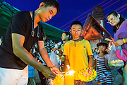 "17 NOVEMBER 2013 - BANGKOK, THAILAND: People light the candles on their krathongs before floating them in the Chao Phraya River near Wat Yannawa in Bangkok. Loy Krathong (also written as Loi Krathong) is celebrated annually throughout Thailand and certain parts of Laos and Burma (in Shan State). The name could be translated ""Floating Crown"" or ""Floating Decoration"" and comes from the tradition of making buoyant decorations which are then floated on a river. Loi Krathong takes place on the evening of the full moon of the 12th month in the traditional and they do this all evening on the 12th month Thai lunar calendar. In the western calendar this usually falls in November. The candle venerates the Buddha with light, while the krathong's floating symbolizes letting go of all one's hatred, anger, and defilements       PHOTO BY JACK KURTZ"