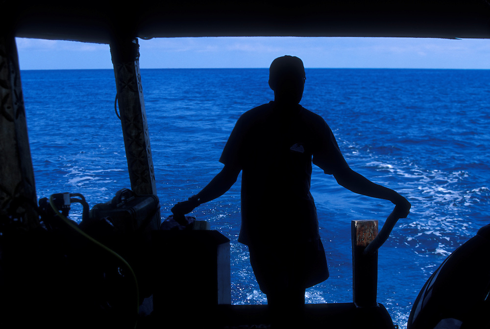 Africa, Tanzania, Zanzibar, Matemwe Bay, Silhouette of boat captain piloting charter boat on Indian Ocean