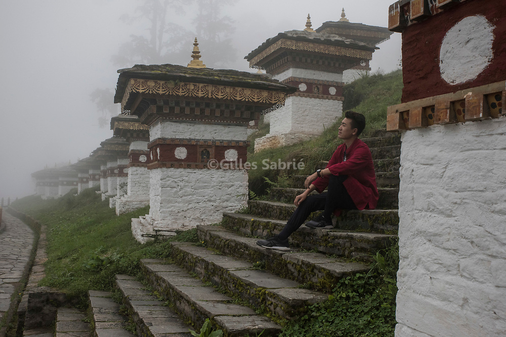 For a story by Steven Lee Myers, Bhutan<br /> Dochula pass, Bhutan, August 2nd, 2017<br /> Ji Xing, a 25 years old student from Beijing sitting near typical Bhutanese chortens (stupas) at the Dochula pass. Ji Xing has come with a friend on a 5 day tour of Bhutan during his summer holidays. In 2016 Chinese tourists topped the charts of dollar paying tourists in Bhutan. Tourism is a main contributor to Bhutan GDP.<br /> Gilles Sabri&eacute; pour The New York Times