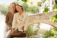 Tourist Couple sitting on wall by Stone Bridge Granada Spain portrait