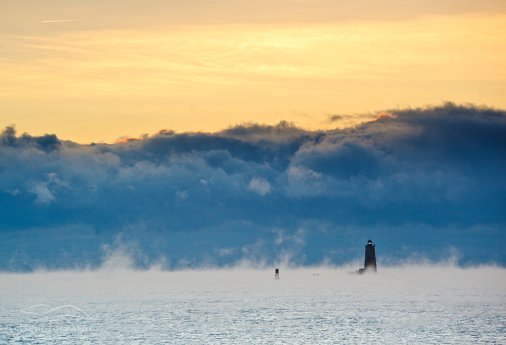 Fog behind Whaleback Light as seen from Great Island Common in New Castle New Hampshire. Sunrise.