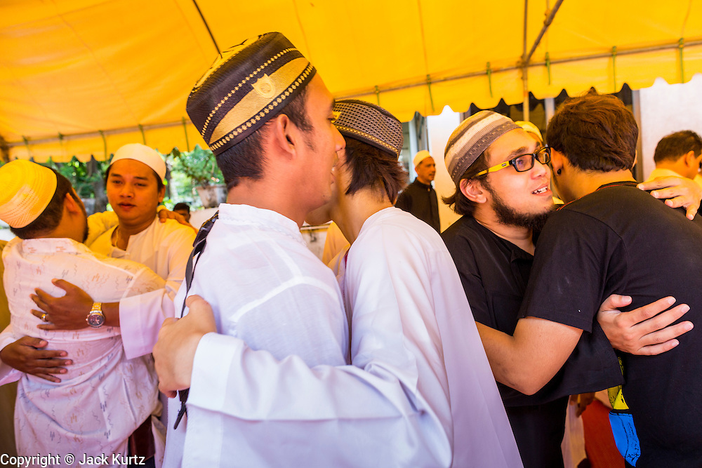 """08 AUGUST 2013 - BANGKOK, THAILAND: Men greet each other after Eid al-Fitr services at Haroon Mosque in Bangkok. Eid al-Fitr is the """"festival of breaking of the fast,"""" it's also called the Lesser Eid. It's an important religious holiday celebrated by Muslims worldwide that marks the end of Ramadan, the Islamic holy month of fasting. The religious Eid is a single day and Muslims are not permitted to fast that day. The holiday celebrates the conclusion of the 29 or 30 days of dawn-to-sunset fasting during the entire month of Ramadan. This is a day when Muslims around the world show a common goal of unity. The date for the start of any lunar Hijri month varies based on the observation of new moon by local religious authorities, so the exact day of celebration varies by locality.       PHOTO BY JACK KURTZ"""