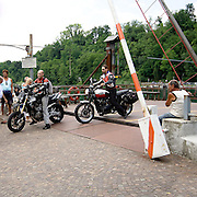 Motociclisti scendono dal traghetto di Imbersago..Two bikers descending from Imbersago ferry, built following Leonardo da Vinci criteria that exploit the power of water to push the ferry without any engine.