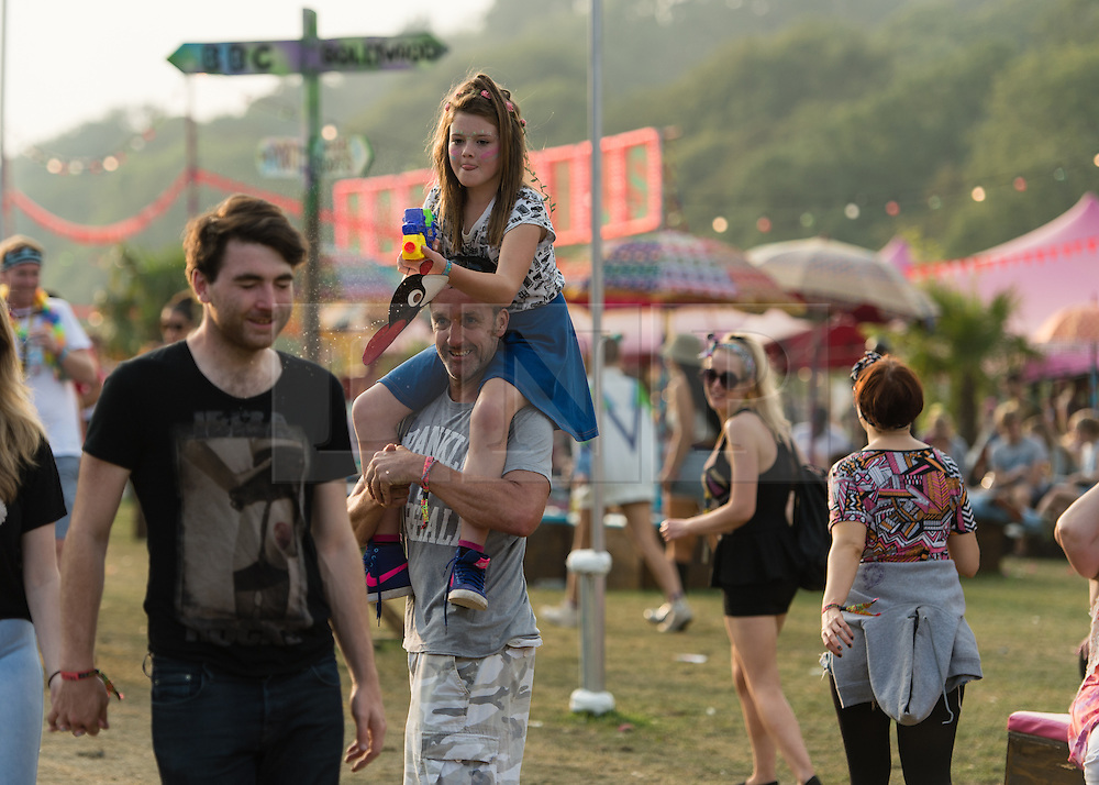 © Licensed to London News Pictures. 07/09/2014. Isle of Wight, UK. At Bestival 2014 daughter a shoots a water pistol at people on a warm sunny afternoon as her father carries her on her shoulders on Day 4 Sunday the final day of the festival. This weekend's headliners include Chic featuring Nile Rodgers, Foals and Outcast.   Bestival is a four-day music festival held at the Robin Hill country park on the Isle of Wight, England. It has been held annually in late summer since 2004.    Photo credit : Richard Isaac/LNP