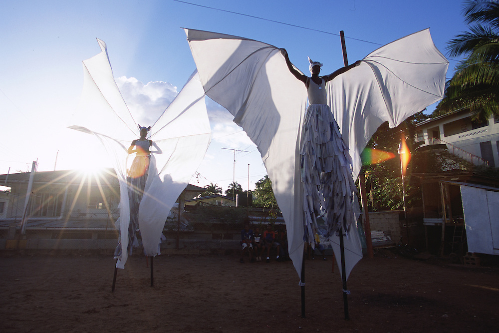 """Trinidad and Tobago """"MOKO JUMBIES: The Dancing Spirits of Trinidad"""".(Rodney Barrow - right -, in his custom-made White Bat costume, deploys his fabric wings in front of John Sterling, who is testing his Jumbie Bat gear as the rays of the setting sun outline the stunning shapes of the twenty foot wingspan.).A photo essay about a stilt walking school in Cocorite, Trinidad..Dragon Glen de Souza founded the Keylemanjahro School of Art & Culture in 1986. The main purpose of the school is to keep children off the streets and away from drugs..He first taught dances like the Calypso, African dance and the jig with his former partner Cathy Ann Samuel.  Searching for other activities to engage the children in, he rediscovered the art of stilt-walking, a tradition known in West Africa as the Moko Jumbies , protectors of the villages and participants in religious ceremonies. The art was brought to Trinidad by the slave trade and soon forgotten..Today Dragon's school has over 100 members from age 4 and up..His 2 year old son Mutawakkil is probably the youngest Moko Jumbie ever. The stilts are made by Dragon and his students and can be as high as 12-15 feet. The children show their artistic talents mostly at the annual Carnival, which today is unthinkable without the presence of the Moko Jumbies. A band can have up to 80 children on stilts and they have won many of the prestigious prizes and trophies that are awarded by the National Carnival Commission. Designers like  Peter Minshall , Brian Mac Farlane and Laura Anderson Barbata create dazzling costumes for the school which are admired by thousands of  spectators. Besides stilt-walking the children learn the limbo dance, drumming, fire blowing and how to ride  unicycles..The school is situated in Cocorite, a suburb of Port of Spain, the capital of Trinidad and Tobago..all images © Stefan Falke"""