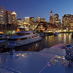 Large luxury yachts reflect Boston's skyline in Boston Harbor.