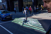 In an area of reflected light, a man crosses Threadneedle Street in front of stopped traffic in the City of London - the capital's financial centre (aka The Square Mile), on 27th September 2018, in London, England.