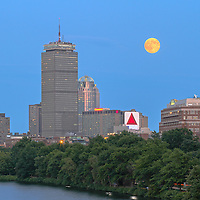 Boston skyline photography showing a full moon across the cityscape of historic landmarks such as the Prudential Center, Citgo Sign and Boston University on a beautiful summer night.<br />