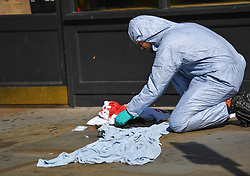 © Licensed to London News Pictures. 13/09/2018. London, UK. A forensic investigator works amongst blood stained clothing at the scene of a double stabbing that happened in the early hours of the morning outside Shepherd's Bush tube station. A man in his early thirties was arrested on suspicion of two counts of grievous bodily harm, he remains in police custody. Photo credit: Guilhem Baker/LNP