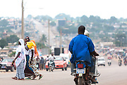 Women walk across a street in Bouake, Cote d'Ivoire on Sunday July 14, 2013.
