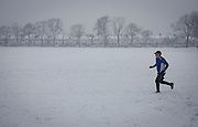 A middle-aged man jogs through fresh snow in his local south London park during bad weather. With a line of Edwardian period homes  beneath 100 year-old ash trees at the bottom of this hill in Ruskin Park, south London, the man runs easily in the powder wearing suitable winter sports clothing and a peaked cap. It is a bleak mid-winter and exercise in these freezing temperatures can be exhilarating if not too slippery.  .