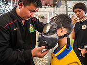 "14 JANUARY 2017 - BANGKOK, THAILAND: A Thai soldier helps child put on gas mask during Children's Day activities at the King's Guard, 2nd Cavalry Division base in Bangkok. Thailand National Children's Day is celebrated on the second Saturday in January. Known as ""Wan Dek"" in Thailand, Children's Day is celebrated to give children the opportunity to have fun and to create awareness about their significant role towards the development of the country. Many government offices open to tours and military bases hold special children's day events. It was established as a holiday in 1955.        PHOTO BY JACK KURTZ"