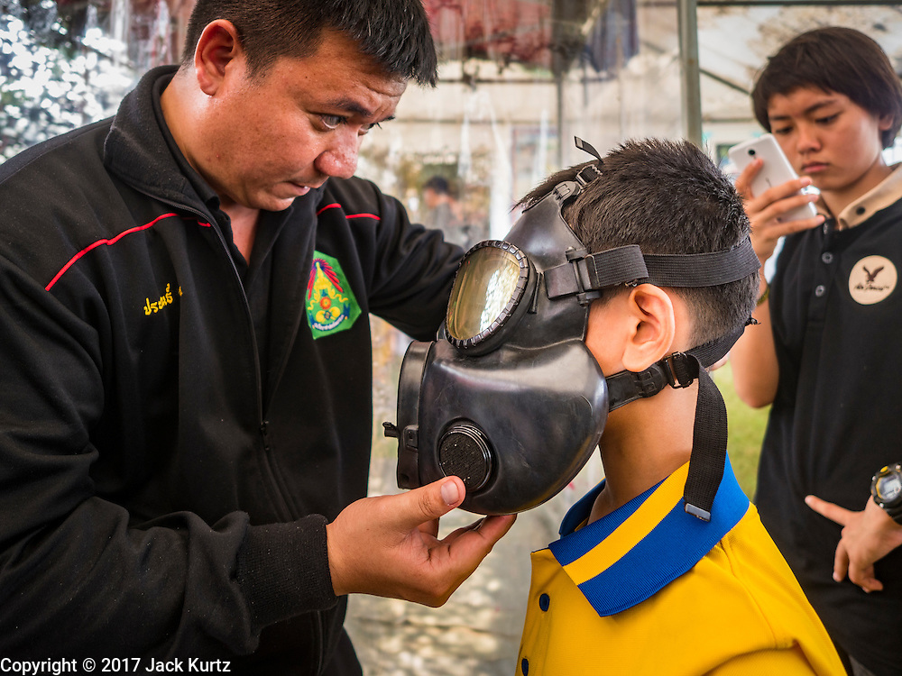 """14 JANUARY 2017 - BANGKOK, THAILAND: A Thai soldier helps child put on gas mask during Children's Day activities at the King's Guard, 2nd Cavalry Division base in Bangkok. Thailand National Children's Day is celebrated on the second Saturday in January. Known as """"Wan Dek"""" in Thailand, Children's Day is celebrated to give children the opportunity to have fun and to create awareness about their significant role towards the development of the country. Many government offices open to tours and military bases hold special children's day events. It was established as a holiday in 1955.        PHOTO BY JACK KURTZ"""