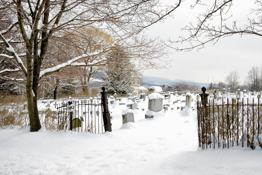 An early Spring snowfall at a cemetery entrance with the buds of March showing some color on the trees making a peaceful landscape.