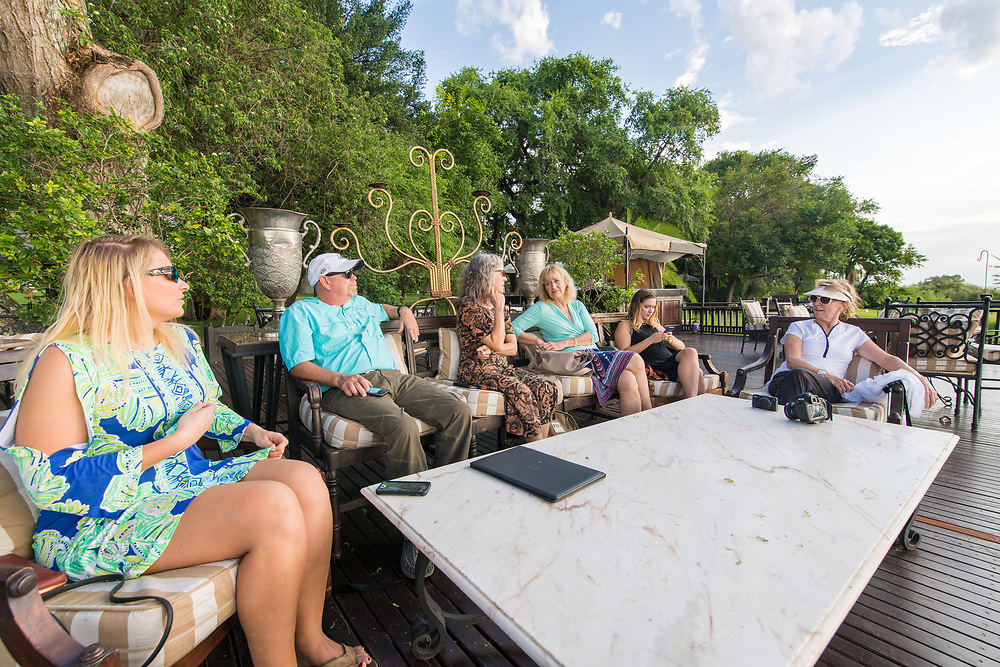 A group of tourists sit and chat on the sundeck of the Royal Livingstone Hotel in Livingstone, Zambia