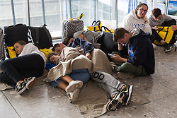 Passengers sleep on the floor of the departures hall at Terminal 5 at Heathrow Airport after an IT glitch brings British Airways systems to a halt, causing disruption to thousands of passengers with flights cancelled and delayed. London, August 07 2019.