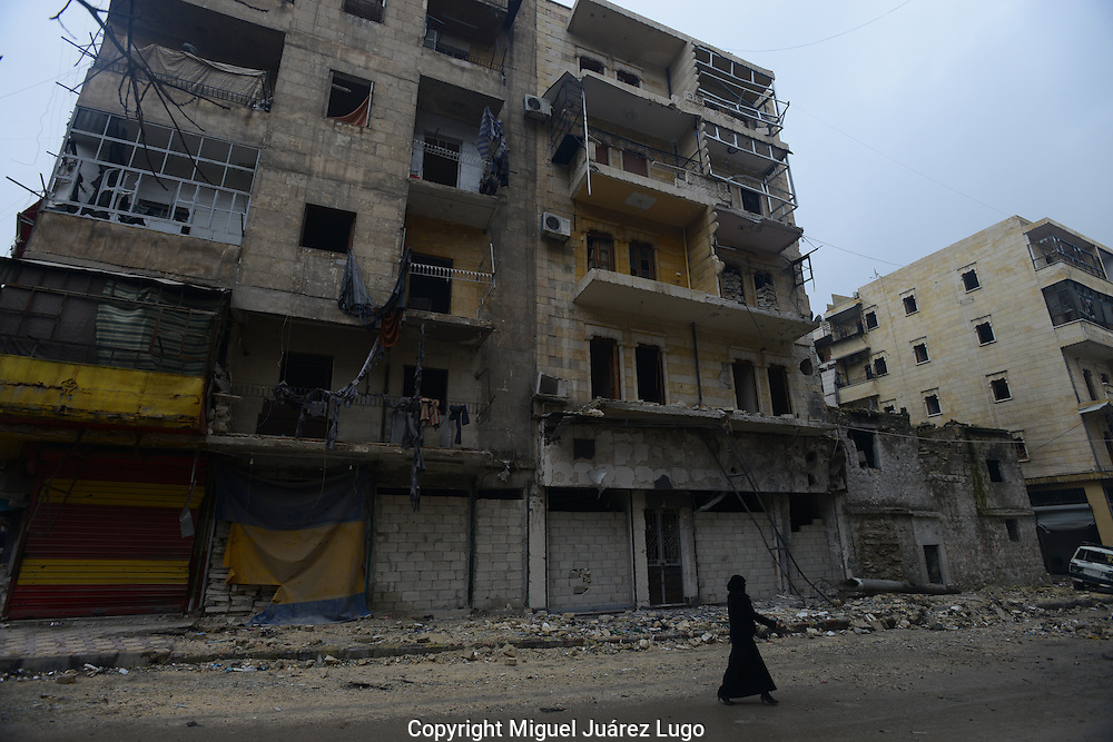 Aleppo, Syria, December, 2012. A woman walks in the Alshaar neighborhood of this city. The area is near the ruins of the Dar Al Sheffaa hospital where more than 30 people died after a Syrian government aerial bombardment almost a month ago. (Photo by Miguel Juárez Lugo)