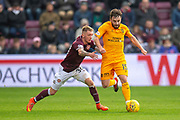 Callumn Morrison (#38) of Heart of Midlothian tries to grab Steven Lawless (#15) of Livingston FC during the 4th round of the William Hill Scottish Cup match between Heart of Midlothian and Livingston at Tynecastle Stadium, Edinburgh, Scotland on 20 January 2019.