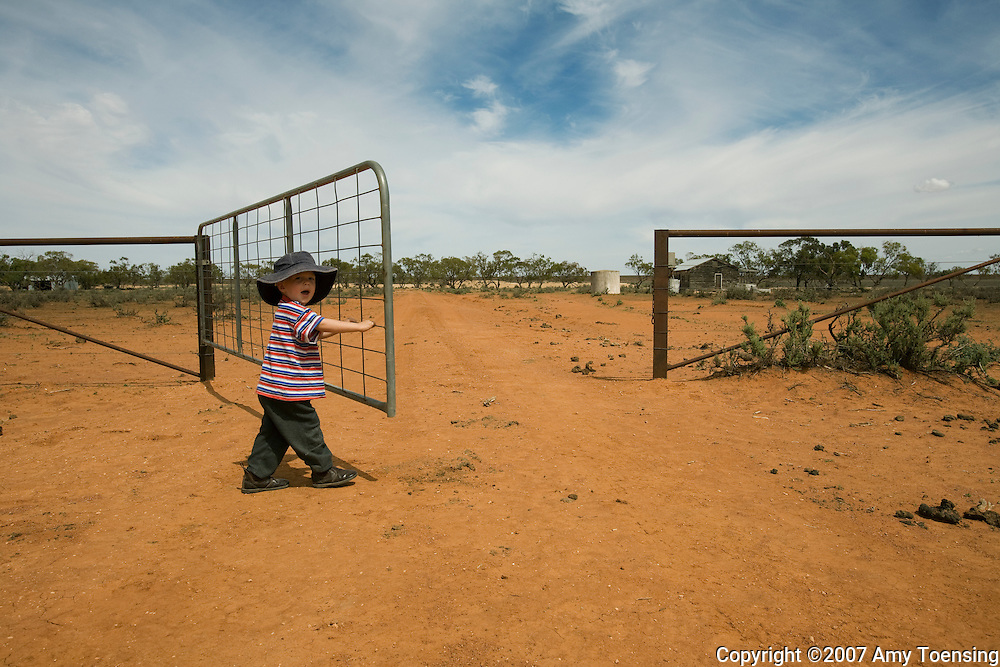IVANHOE, NSW, AUSTRALIA - FEBRUARY 7: Riley Turner opens a gate for his mom to drive their truck through on the Turner family's farm February 7, 2008 in Ivanhoe, New South Wales, Australia. The Turners, like many farm families in the Murray-Darling Basin have had to move most of their livestock to other regions of Australia because their own land is too dry to produce feed after years of drought. The Murray-Darling Basin of Australia has been plagued with severe drought since the late 1990's. (Photo by Amy Toensing/ Reportage by Getty Images). _________________________________<br />