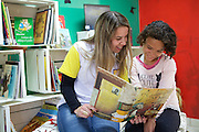C&A Instituto volunteer reading to Marcia at her community library, Biblioteca Chocolatao, Porte Alegre.
