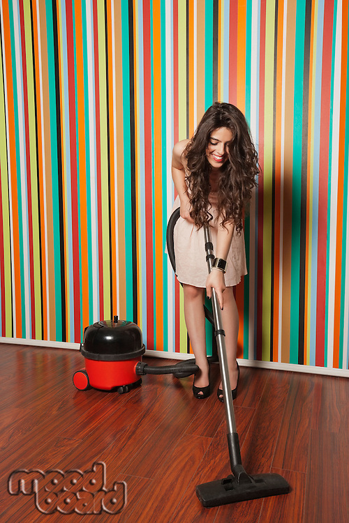 Happy young woman cleaning hardwood floor using vacuum cleaner