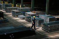 SANTA MARIA DEGLI ANGELI (ASSISI), ITALY - 11 JUNE 2018: A worker walks by steel sheets at the IRON S.p.A. factory, a publicly traded company that makes industrial steel parts, in Santa Maria degli Angeli (Assisi), Italy, on June 11th 2018.<br /> <br /> President Donald Trump's administration plans to impose tariffs on European steel and aluminum imports after failing to win concessions from the European Union, a move that could provoke retaliatory tariffs and inflame trans-Atlantic trade tensions. Until the moment that the American president rendered his decision, Mr. Capponi, the commercial director of IRON spa, was confident the continent would be spared.<br /> Given that IRON is a purchaser of steel, the company might benefit from the American tariffs. Steel now shipped to the United States from mills within Europe might stay here to avoid the tariffs, raising the supply and dropping prices. Chinese producers who export to American shores could divert their product to Europe, amplifying this trend.<br /> But Mr. Capponi was banking on none of this. Even if steel prices decline, his customers are likely to squeeze him for lower prices. More broadly, the American tariffs — justified by the Trump administration as a supposed defense of national security — reverberated as a blow against world trade.