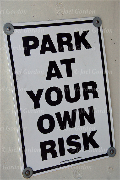 "warning sign, "" Park At Your Own Risk"" at a parking garage"