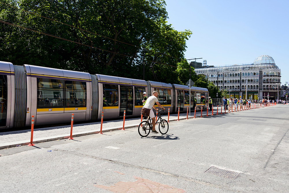 June 17th, 2017. Dublin, Ireland. At Stephen's Green, the Cross City Luas project undergoes testing with a full tram on the newly completed tracks. A contingent of engineers walks with the tram and they carry out various checks as members of the public look on and watch the going on. The cross city Luas project is a four year project conducted to join up the two existing tram lines in Dublin city, and bring trams  and passengers from the south side to the north side on the Luas system.