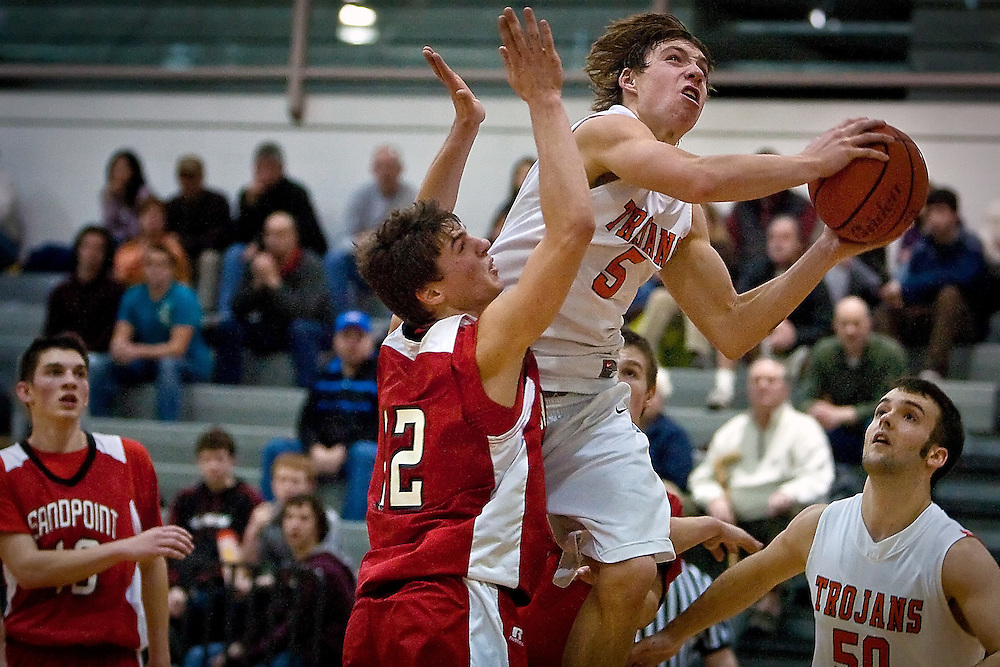 JEROME A. POLLOS/Press..Post Falls High's Connor Hill flies toward the rim after blowing past Stefan Buratto from Sandpoint High during the second half of the Trojans 94-75 overtime win Wednesday.