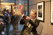 Andy Summers, former guitar player of the Police, writer and photographer, poses taking pictures at Leica Gallery where there is an exhibition of his photographs in Milan, March 22, 2016. &copy; Carlo Cerchioli<br />