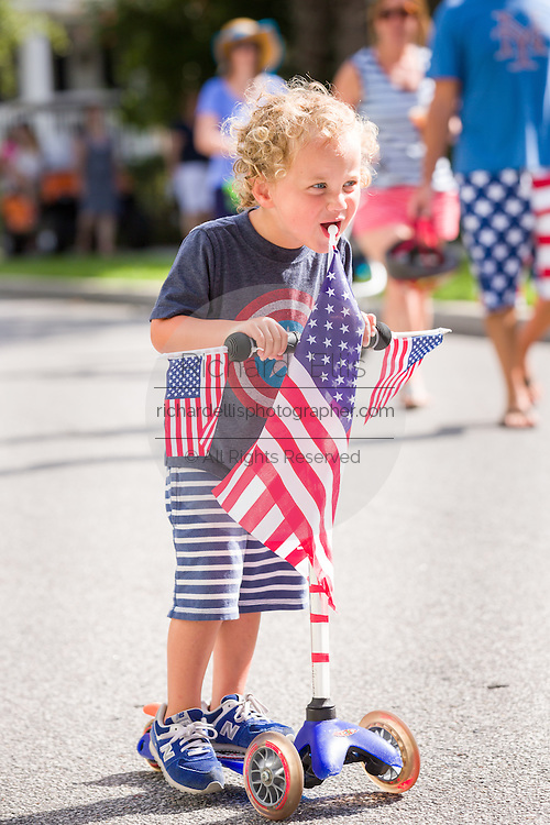 A young boy rides a push scooter decorated in red, white and blue during the I'On neighborhood Independence Day parade July 4, 2015 in Mt Pleasant, South Carolina.
