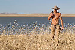 very handsome cowboy without a shirt walking by a lake on a ranch in New Mexico