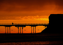 © Licensed to London News Pictures. <br /> 20/09/2017 <br /> Saltburn by the Sea, UK.  <br /> <br /> A brief but dramatic sky is lit up over the pier and Huntcliff in Saltburn by the Sea as the sun begins to rise.<br /> <br /> Photo credit: Ian Forsyth/LNP