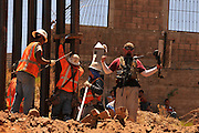 Workers replace a 2.8 mile section of landing matt border wall constructed in 1994 in Nogales, Arizona, USA, at Sonora, Mexico.  Under tight security on the Arizona side of the border, the construction draws much interest from residents of Nogales, Sonora, Mexico.  The concrete marker originally designated the border.