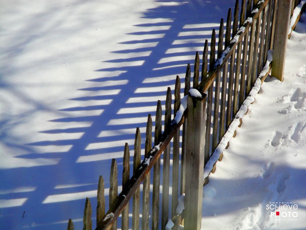 Wooden picket fence in winter sun.